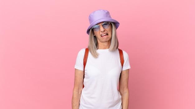 Witte haarvrouw van middelbare leeftijd die zich verbaasd en verward voelt. zomer concept