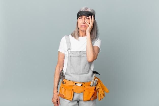 Witte haarvrouw van middelbare leeftijd die zich verveeld, gefrustreerd en slaperig voelt na een vermoeiende en het dragen van werkkleding en gereedschap. huishoudconcept