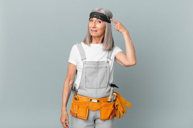 Witte haarvrouw van middelbare leeftijd die zich verward en verbaasd voelt, laat zien dat je gek bent en werkkleding en gereedschap draagt. huishoudconcept