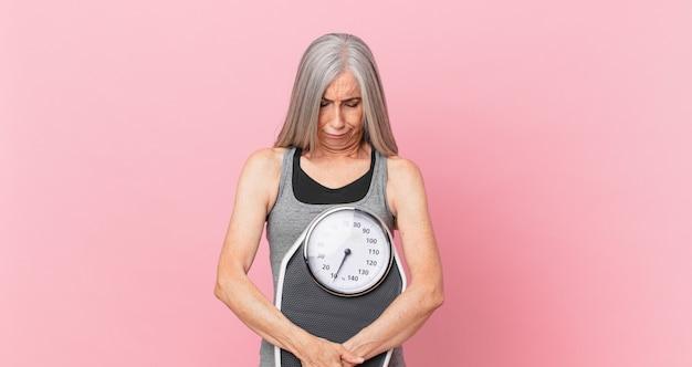Witte haarvrouw van middelbare leeftijd met een weegschaal. fitness- en dieetconcept