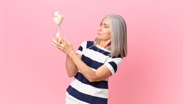 Witte haarvrouw van middelbare leeftijd met een zandlopertimer