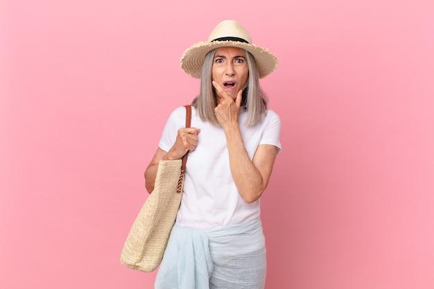Witte haarvrouw van middelbare leeftijd met wijd open mond en ogen en hand op kin. zomer concept