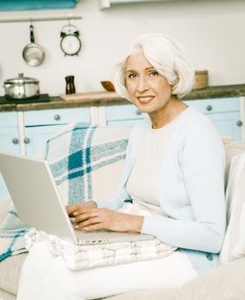 Witte haired vrouw die laptop met behulp van