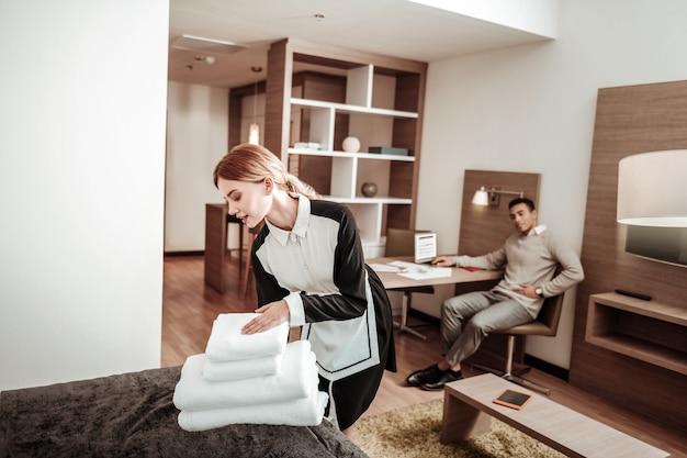 Witte handdoeken meebrengen. aangename hardwerkende huishoudster die nieuwe witte handdoeken naar de kamer van de zakenman brengt