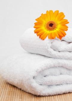 Witte handdoeken onder een oranje zonnebloem