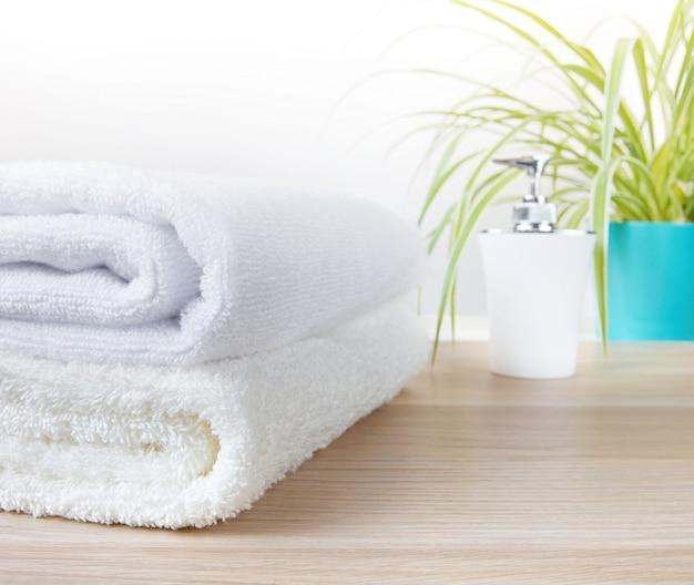 Witte handdoeken op houten tafel in de badkamer met zeepdispenser en groene plantenpot op onscherpe achtergrond.