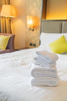 Witte handdoekvouw op bed in hoteltoevlucht