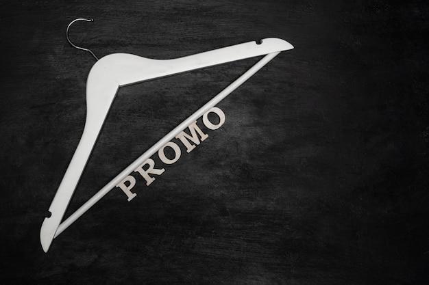 Witte hanger en inscriptie promo op zwarte achtergrond. aandelen, kortingen.