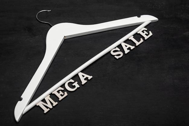 Witte hanger en tekst mega sale op zwarte achtergrond. kortingen. seizoensgebonden verkoop. zwarte vrijdag.