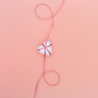 Witte harten, roze lint op pastel roze papier achtergrond.