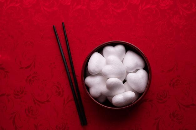 Witte hartvorm op plaat met rode achtergrond, de viering van de de dagvakantie van valentine.