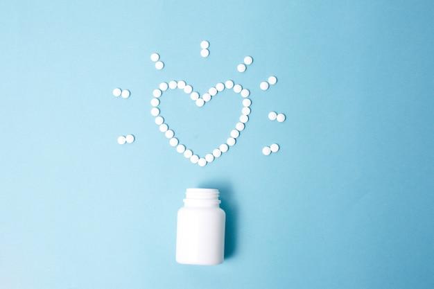 Witte hartvormige tabletten op een blauwe achtergrond