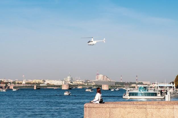 Witte helikopter van het stadsbestuur over de rivier de neva in st. petersburg.