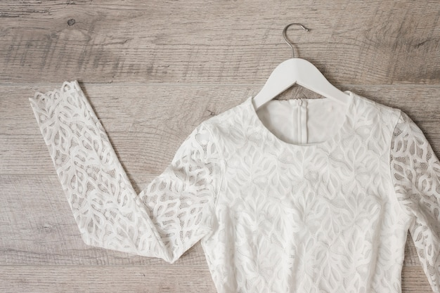 Witte het huwelijkskleding van het kant op kleerhanger tegen houten geweven achtergrond