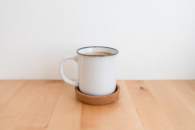 Witte hete koffiekopje op houten tafel en witte muur met kopie ruimte.
