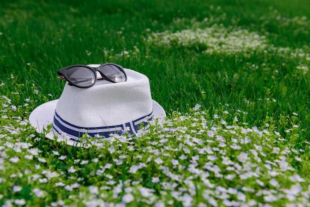 Witte hoed en zonnebril op groen gras en lentebloemen, natuurlijke achtergrond voor recreatie, vakanties