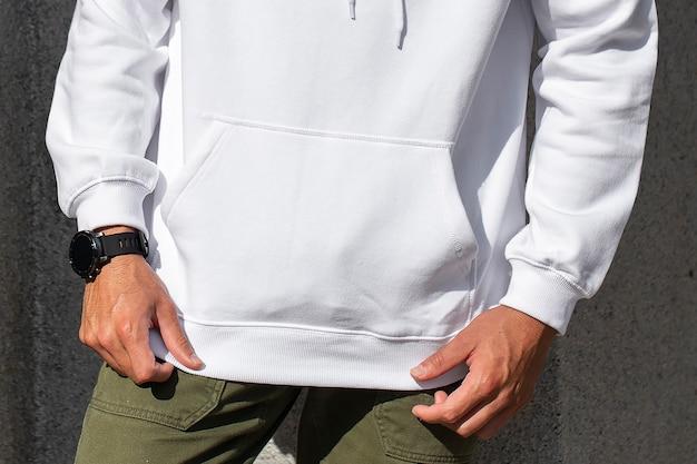 Witte hoodie op man met groene broek close-up fotoshoot