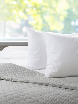 Witte hoofdkussens en blad op een bed met sprei,