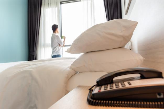 Witte hoofdkussens in hotelruimte met de kop van de mensenholding van koffie die zich bij venster bevinden.