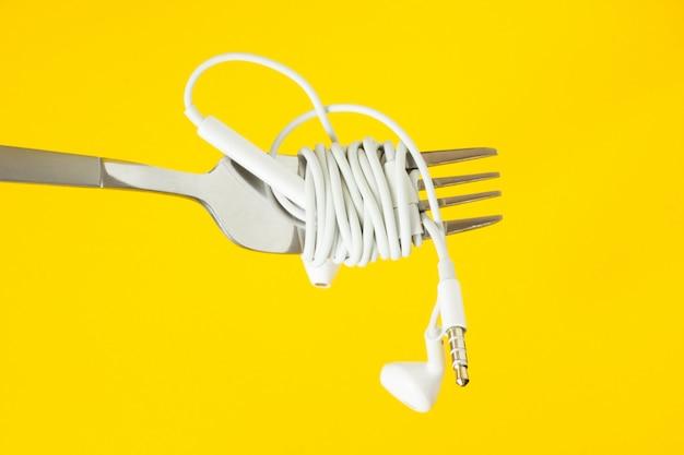 Witte hoofdtelefoons en vork op een gele achtergrond