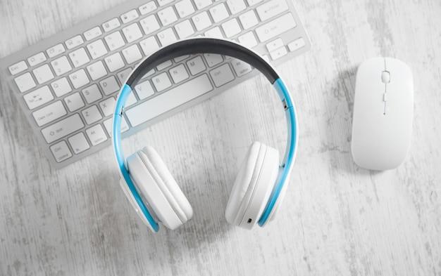 Witte hoofdtelefoons met een computertoetsenbord en muis. zakelijk bureau