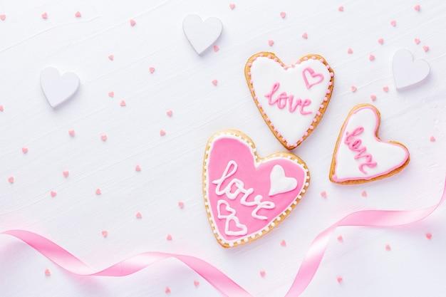 Witte houten achtergrond voor valentijnsdag met hartvormige koekjes met woord liefde en roze lint