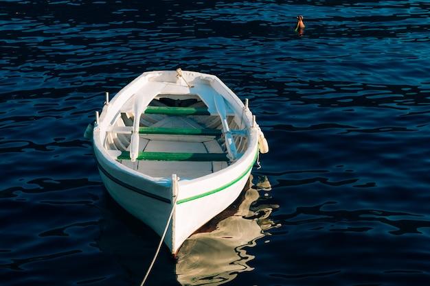 Witte houten boot met roeiriemen vissen op het blauwe water van de baai van kotor in montenegro.
