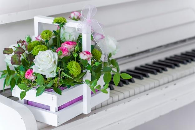 Witte houten doos met boeket witte en roze rozen en chrysanten op witte piano. decoratie van huis. bloemen dozen. bruiloft decoratie