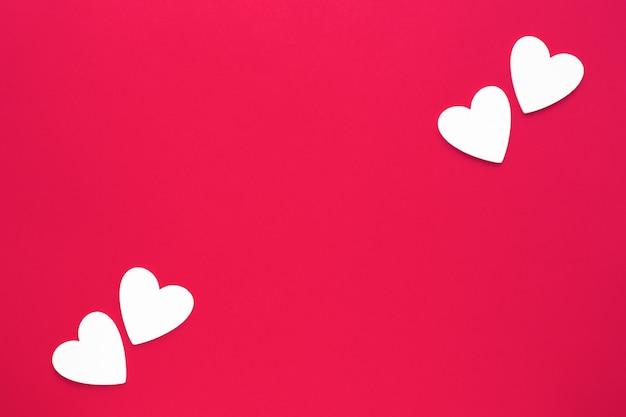Witte houten harten in tegenovergestelde hoeken op heldere rode document achtergrond