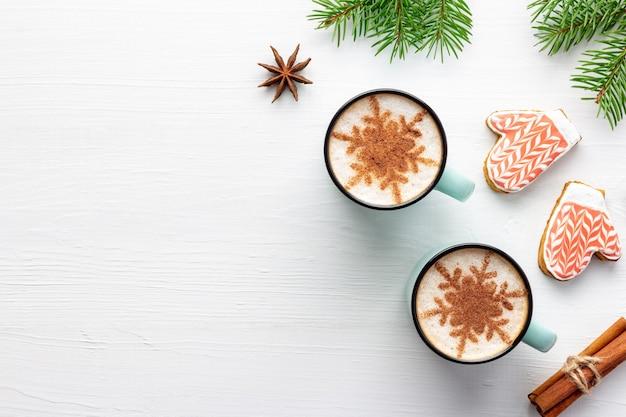 Witte houten kerstmisachtergrond met peperkoek en feestelijke latte met sneeuwvlokken