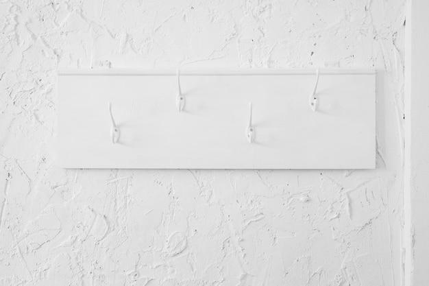 Witte houten kleerhanger met haken op een getextureerde muur.