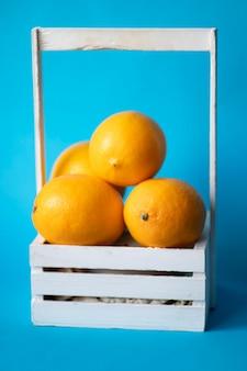 Witte houten mand vol sinaasappels. gele citrusvruchten. rijpe en sappige sinaasappels