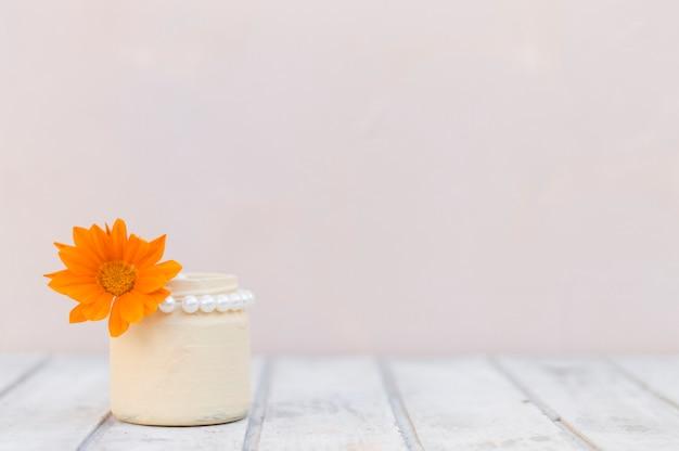 Witte houten oppervlak met vaas en oranje bloem