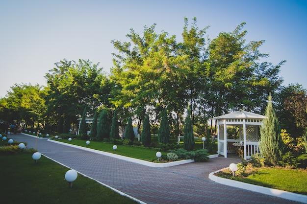 Witte houten prieel op straat in een groen park.