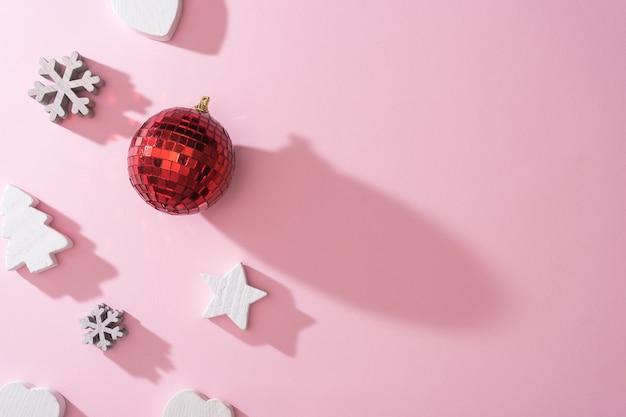 Witte houten sneeuwvlokkenharten en kerstboomdecoratie met rode snuisterij van de discobal op roze achtergrond. minimale nieuwjaar winter vakantie concept. plat leggen.