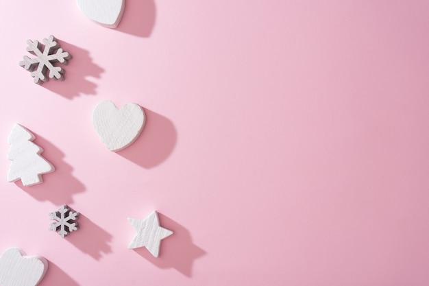 Witte houten sneeuwvlokkenharten en kerstboomdecoratie met roze achtergrond. minimale nieuwjaar winter vakantie concept. plat leggen.