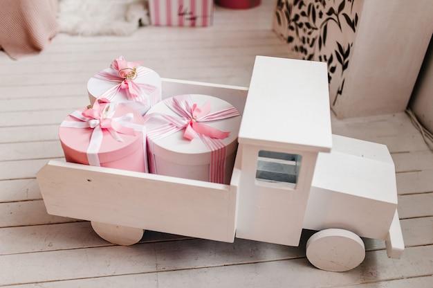 Witte houten speelgoedauto met geschenken. elegante roze dozen achter in de vrachtwagen. verjaardagscadeau. kopieer ruimte, vakantieconcept. kortingen, verkoop.
