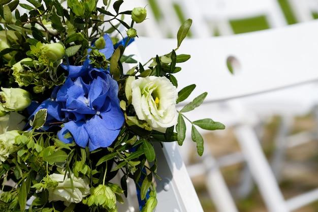 Witte houten stoelen versierd met bloemen en heldere satijnen linten, bruiloft decor tijdens de ceremonie in het dennenbos