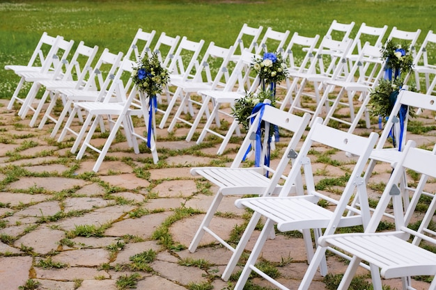 Witte houten stoelen versierd met bloemen en heldere satijnen linten, bruiloft decor tijdens de ceremonie.