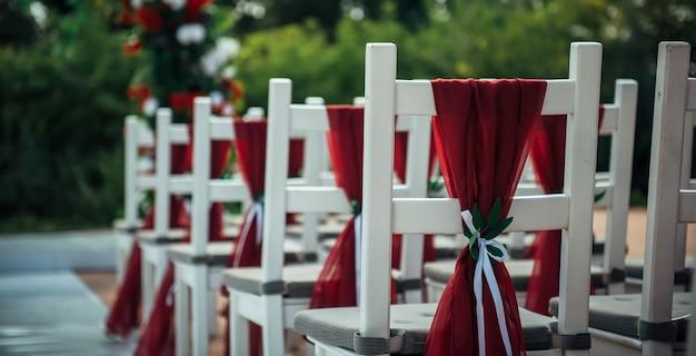 Witte houten stoelen versierd met rode stof en linten voor bruiloftsreceptie buiten. gaststoelen in rijen in het zomerpark.