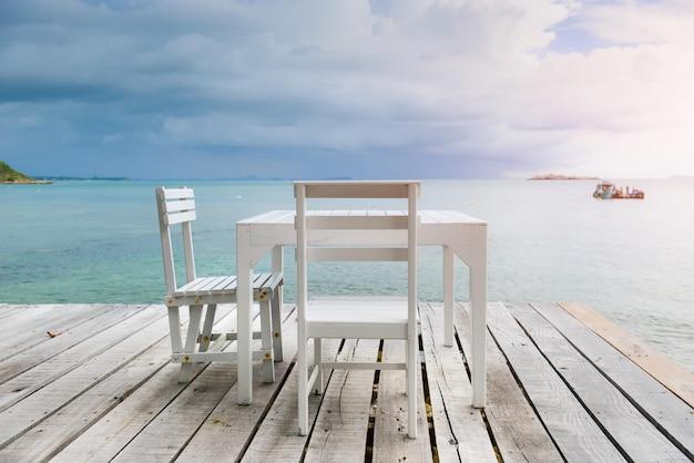 Witte houten tafel en stoelen op het houten balkon van de zee met zeegezicht en blauwe lucht.