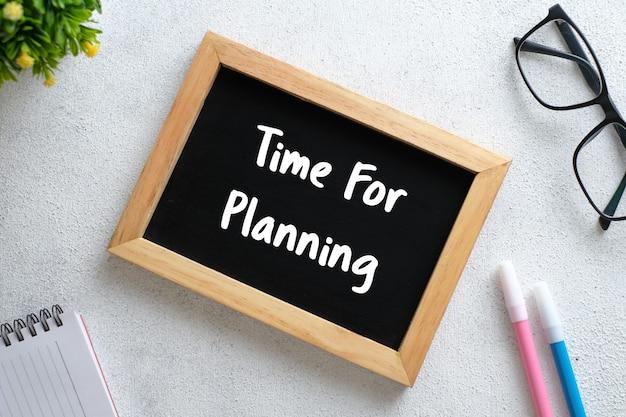 Witte houten tafel met bril, pen, decoratieve planten en krijtbord geschreven met actieplan 2021 goals. bovenaanzicht met kopieerruimte, plat gelegd.