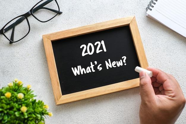 Witte houten tafel met bril, pen, decoratieve planten en krijtbord geschreven over 2021 trends. bovenaanzicht met kopieerruimte, plat gelegd.