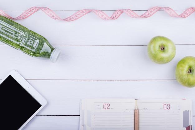 Witte houten tafel met een tablet, notebook, detox en groene appel. bovenaanzicht hoek met kopie ruimte