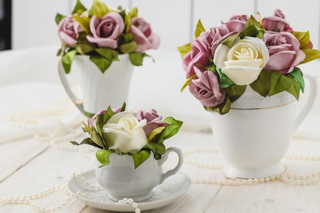Witte houten tafel met roze bloemen, linten en kralen. bruiloft stijl