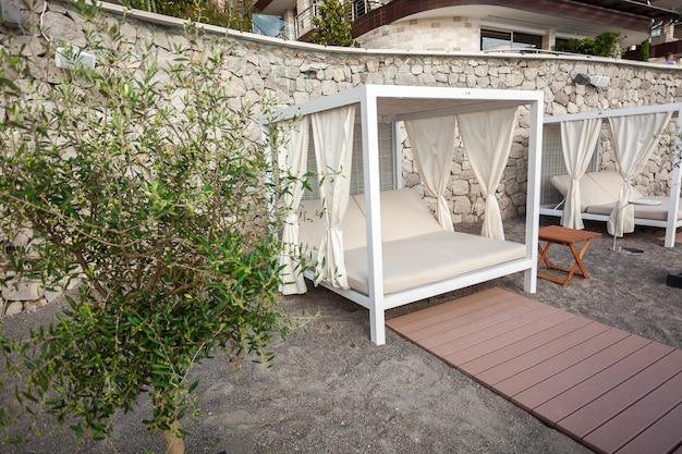 Witte houten tent met ligstoelen op het strand van luxe resort