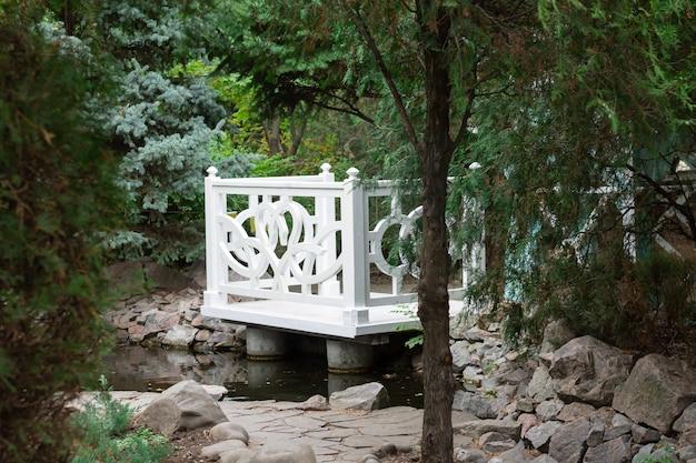 Witte houten tuinhuisje in een zomer groen park. gezellige tuinnis om tijd door te brengen in de natuur