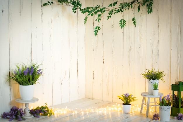 Witte houten wand met bloemen, lavendel, guirlande en lichtjes