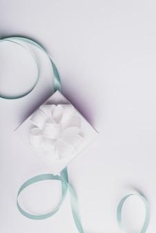 Witte huidige doos met gekruld turkoois lint dat op witte achtergrond wordt geïsoleerd