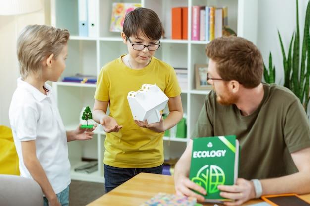Witte huis observeren. geïnteresseerde kleine student die vragen stelt tijdens ecologielessen terwijl ze in de buurt van hun leraar staan